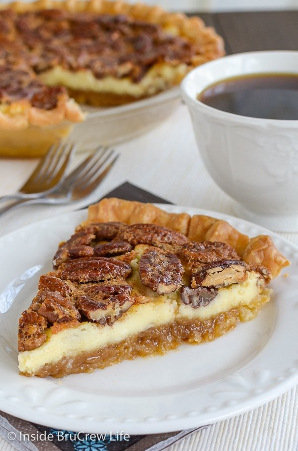 A slice of pecan cheesecake pie on a white plate with the whole pie behind it.