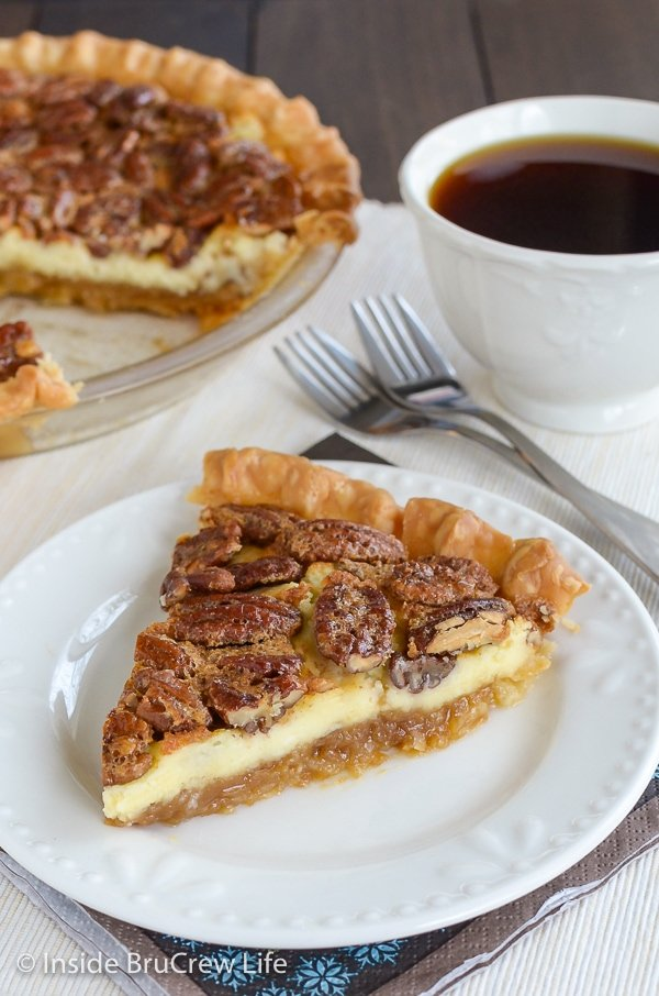 A slice of pecan cheesecake pie on a white plate with a cup of coffee behind it.