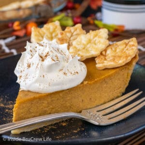 A black plate with a slice of pumpkin pie topped with whipped cream on it