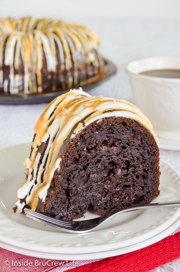 A white plate with a slice of mocha bundt cake topped with white chocolate, caramel, and sea salt.