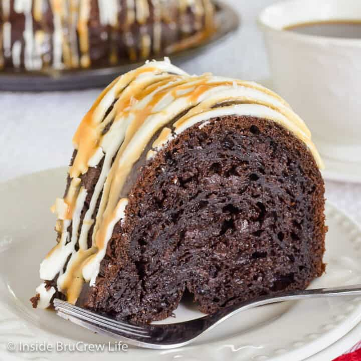 A white plate with a slice of mocha bundt cake topped with caramel, white chocolate, and sea salt.
