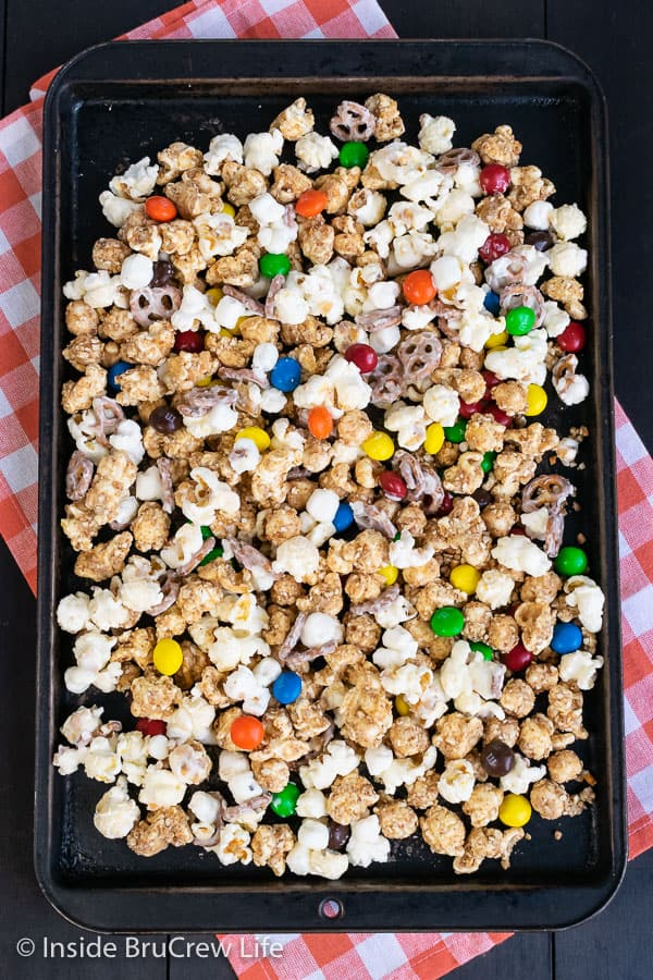 White Chocolate Peanut Butter Pretzel Popcorn - pretzels, peanut butter, and white chocolate give this easy snack mix a fun and delicious coating. Make this no bake recipe for game days or movie nights! #popcorn #chocolatecoveredpopcorn #whitechocolate #peanutbutter #pretzel #gameday #snackmix #nobake