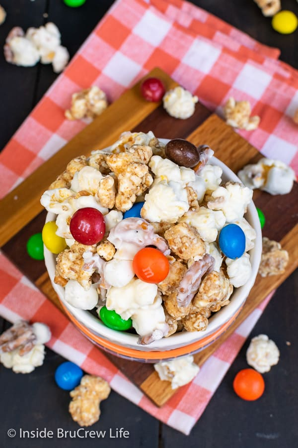 White Chocolate Peanut Butter Pretzel Popcorn - this easy chocolate covered popcorn is loaded with pretzels, marshmallows, and peanut butter candies. Great recipe for game days or movie nights! #popcorn #chocolatecoveredpopcorn #whitechocolate #peanutbutter #pretzel #gameday #snackmix #nobake