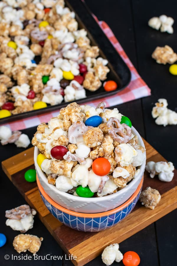 White Chocolate Peanut Butter Pretzel Popcorn - this easy chocolate covered popcorn is loaded with marshmallows, peanut butter candies, and pretzels. Easy recipe to make and snack on during movies or games! #popcorn #chocolatecoveredpopcorn #whitechocolate #peanutbutter #pretzel #gameday #snackmix #nobake
