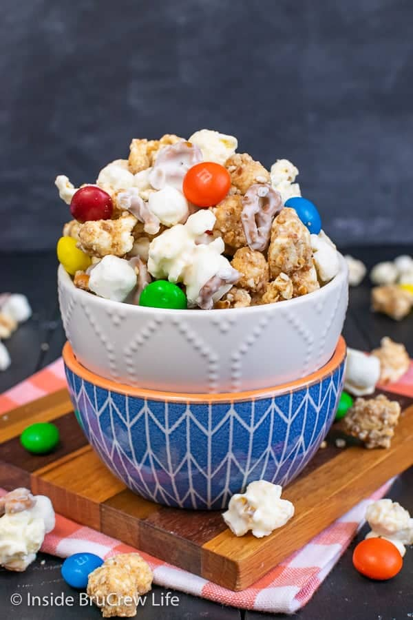 White Chocolate Peanut Butter Pretzel Popcorn - this fun white chocolate covered popcorn is loaded with candies and pretzels. Make this easy no bake recipe to munch on during movies or games. #popcorn #chocolatecoveredpopcorn #whitechocolate #peanutbutter #pretzel #gameday #snackmix #nobake