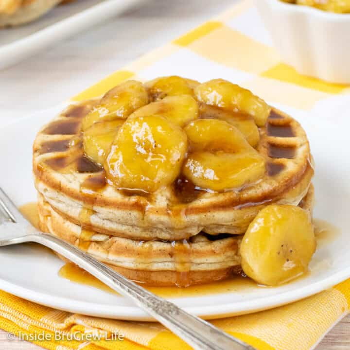 A white plate with two homemade banana waffles and banana slices on it
