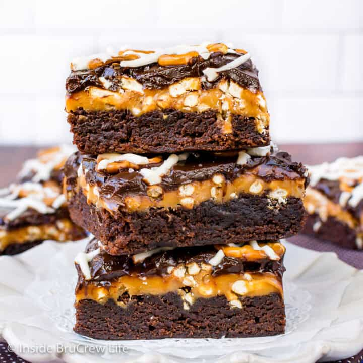 Three salted caramel brownies stacked together on a white plate.
