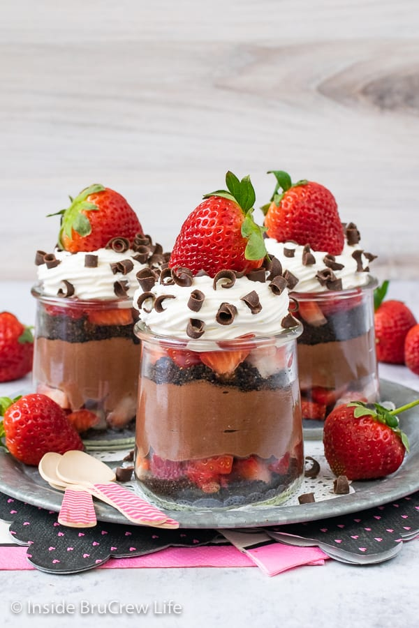 Three clear jars of strawberry chocolate cheesecake parfaits with Cool Whip and a strawberry on a metal tray