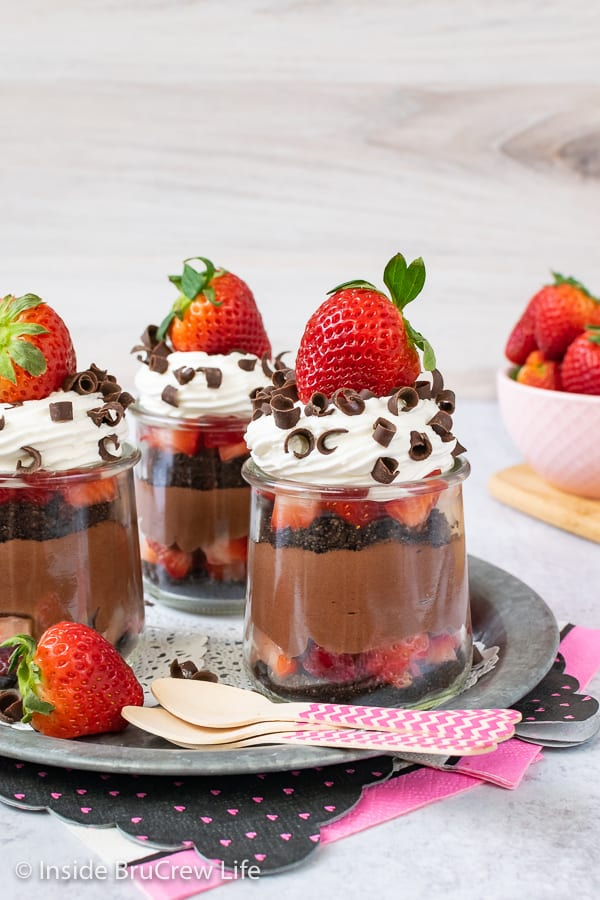 Three clear jars filled with strawberry chocolate cheesecake layers and topped with whipped cream, chocolate curls, and fresh strawberries