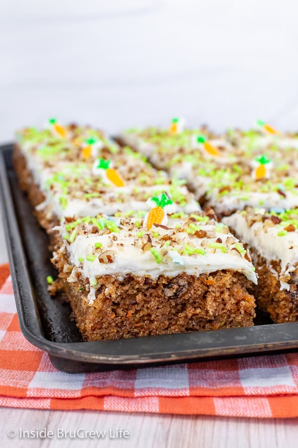 A close up picture of squares of carrot cake bars on a black sheet pan
