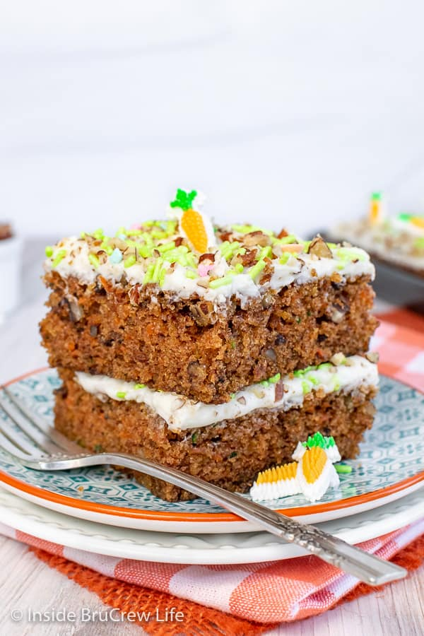 A stack of two carrot cake bars with sprinkles and nuts on a white and teal plate