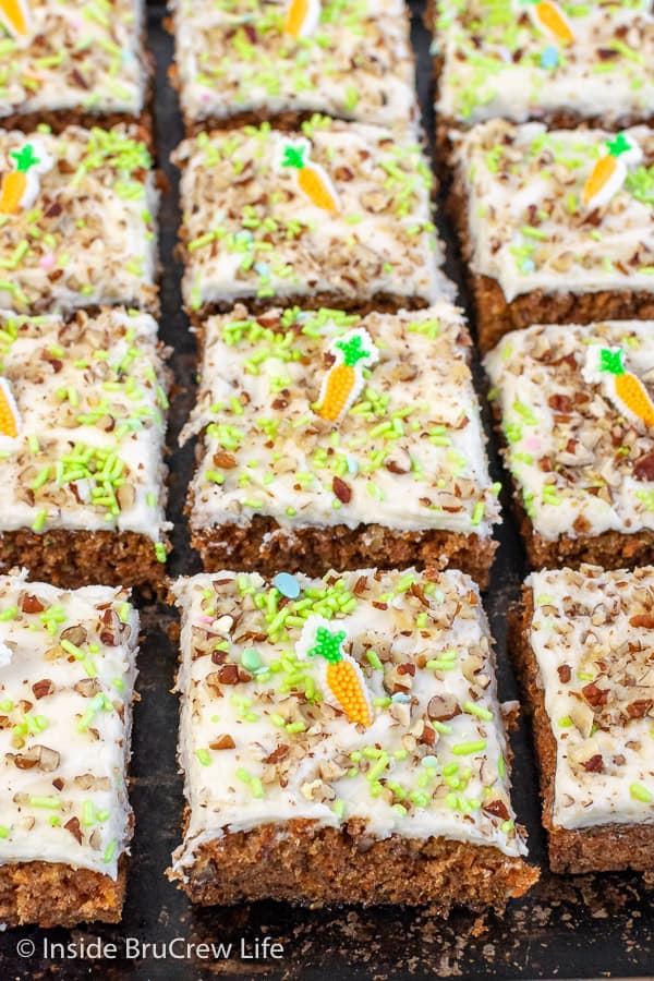 A black sheet pan covered with squares of carrot cake bars topped with frosting, pecans, and green sprinkles