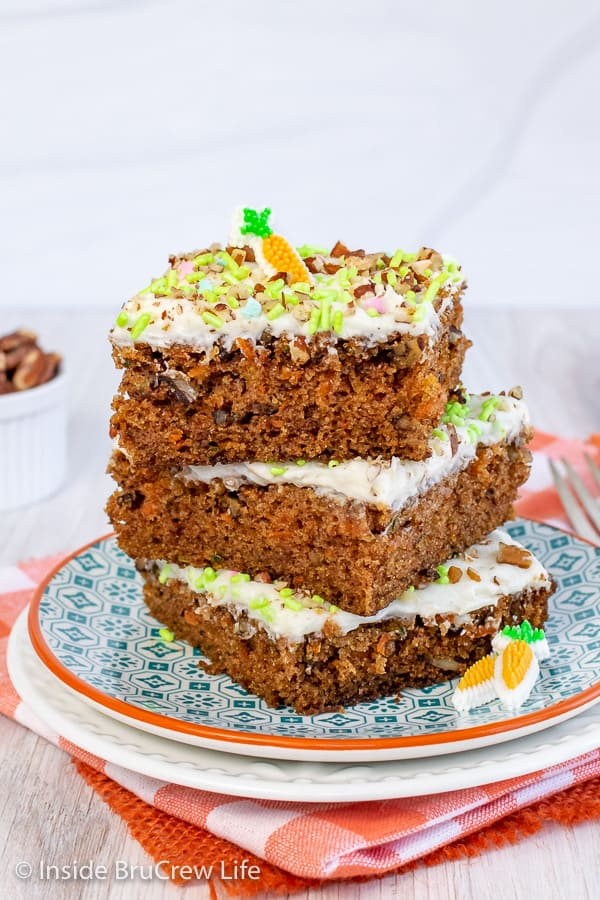 A stack of three carrot cake bars with cream cheese frosting on a white and teal plate