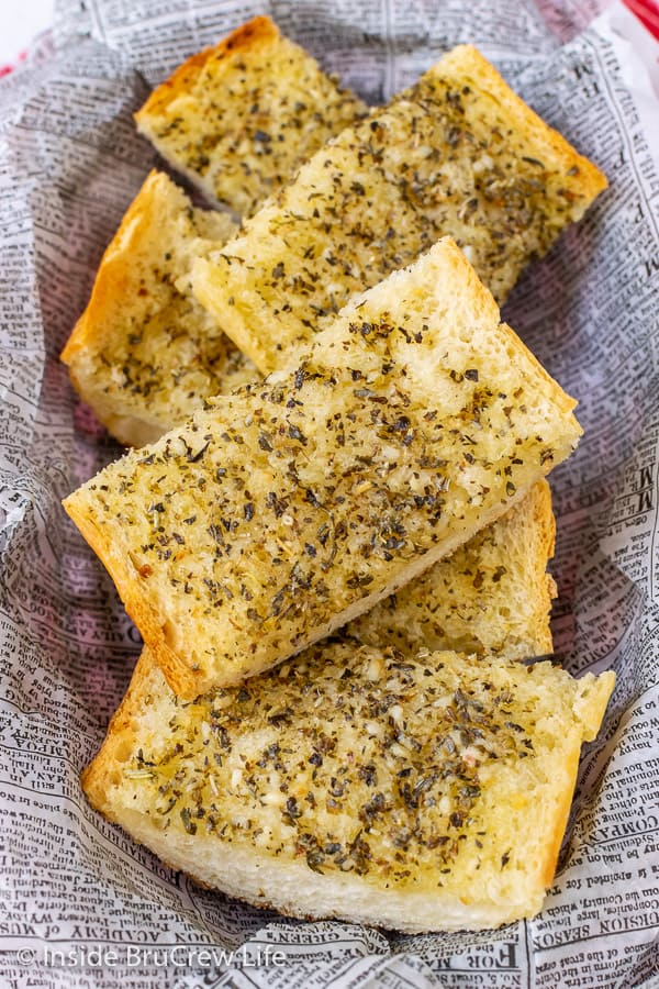 Easy Garlic Herb Bread - a mixture of butter, garlic, and herbs spread on French bread makes a delicious addition to any dinner. Make this easy recipe right before dinner or make it ahead of time and freeze it for later.