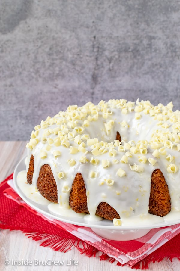 A close up picture of a lemon bundt cake with lemon glaze on a white plate