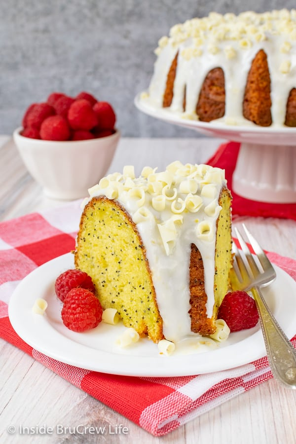 A white plate on a red and white checkered towel with a slice of lemon bundt cake on it