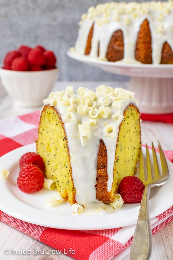 A slice of lemon cake with lemon glaze and fresh raspberries on a white plate with the lemon bundt cake behind it