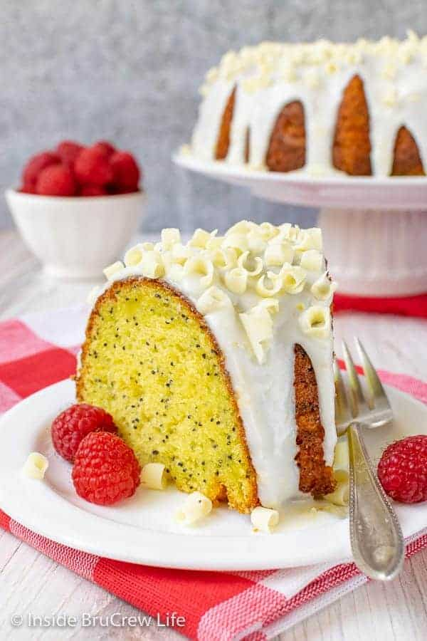 A slice of lemon bundt cake on a white plate with fresh raspberries around it