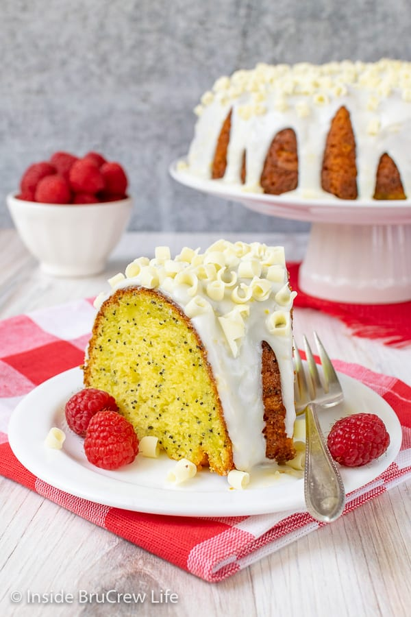 A slice of lemon bundt cake with lemon glaze on a white plate with a bowl of raspberries behind it