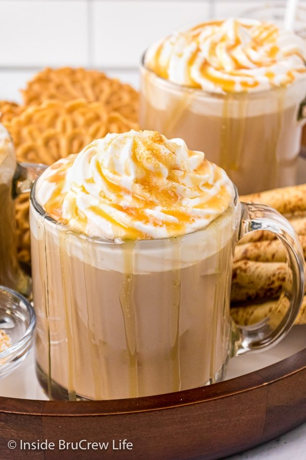 Two clear mugs filled with a homemade caramel latte and topped with whipped cream, caramel drizzles, and sea salt.