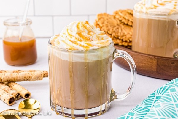 A clear glass mug filled with a homemade latte, whipped cream, and caramel drizzles.