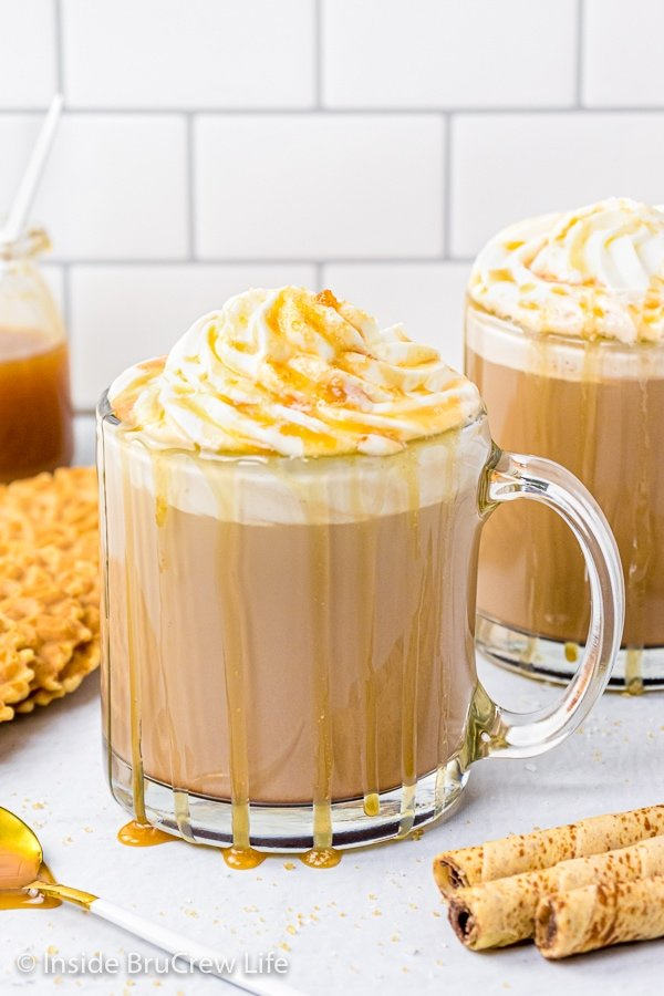 Two clear glass mugs filled with a homemade mocha topped with whipped cream and salted caramel drizzles.