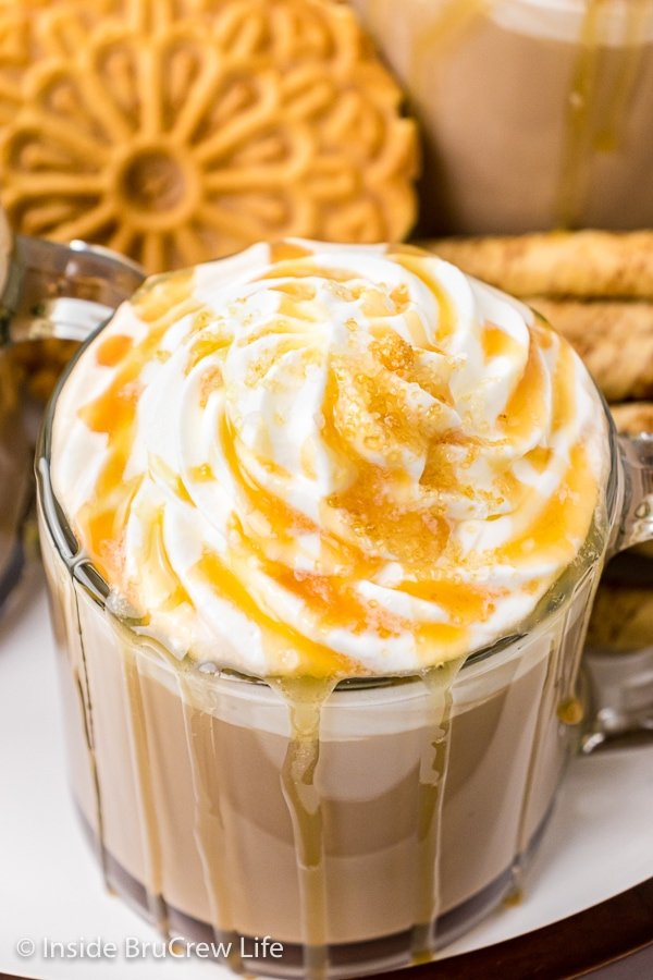 Overhead picture of a homemade caramel latte topped with whipped cream and caramel drizzles.