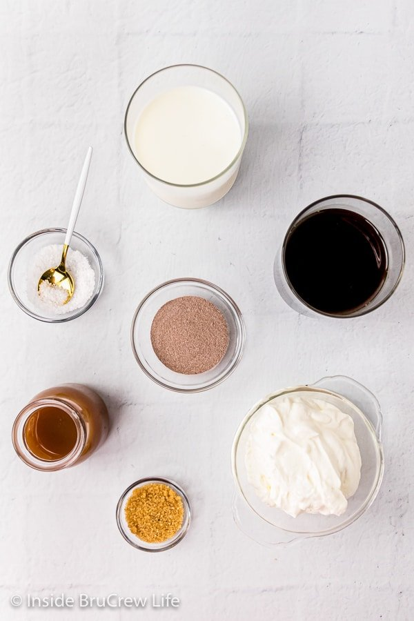 A white board with bowls of ingredients to make a copycat salted caramel mocha latte on it.