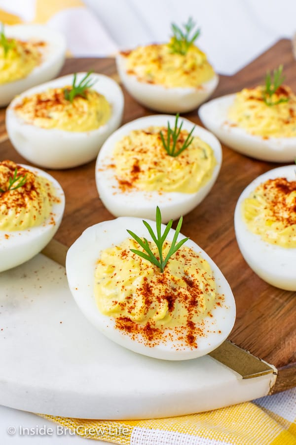Close up picture of deviled eggs with dill and paprika on a white and brown tray