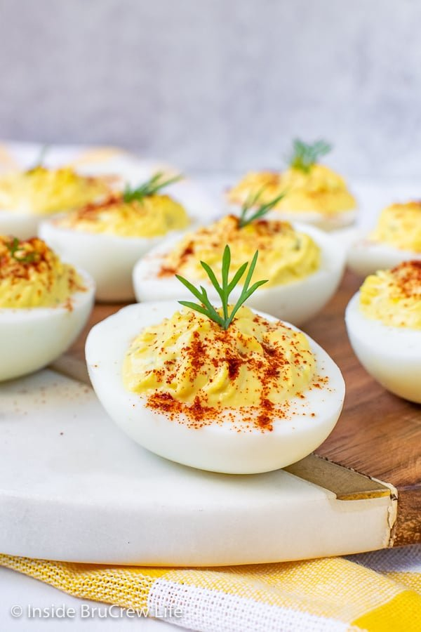 A close up picture of deviled eggs with a sprinkle of paprika and a sprig of dill on a white tray