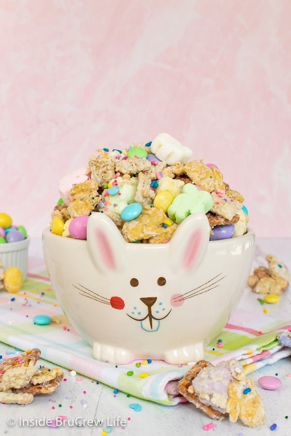 A white bunny bowl filled with Easter snack mix on a colorful towel with a pink board behind it