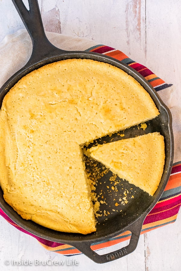 Overhead close up picture of a cast iron skillet with easy cornbread with a wedge cut in it