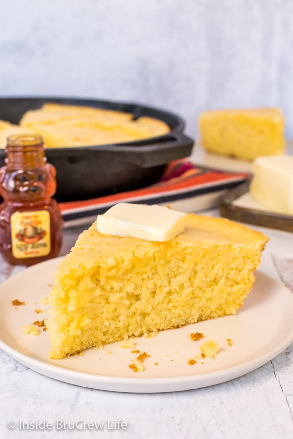 A wedge of easy cornbread with a pat of butter on an off white plate with a skillet of cornbread behind it