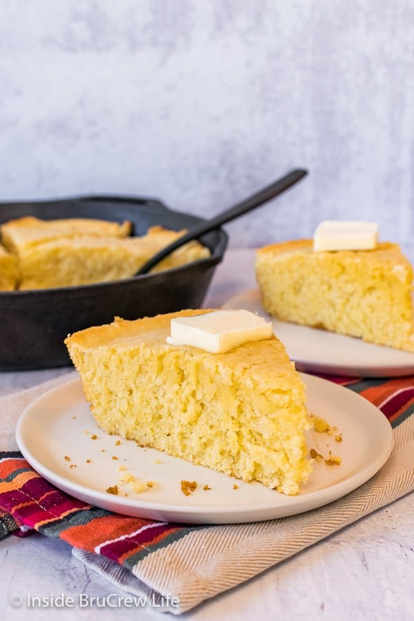 A wedge of easy cornbread on an off white plate with a skillet of cornbread behind it