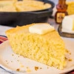 Square photo of a wedge of easy skillet cornbread on an off white plate