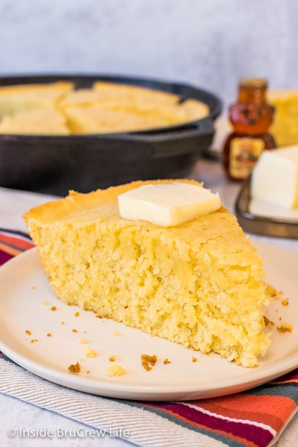 A wedge of skillet cornbread on an off white plate with the skillet behind it