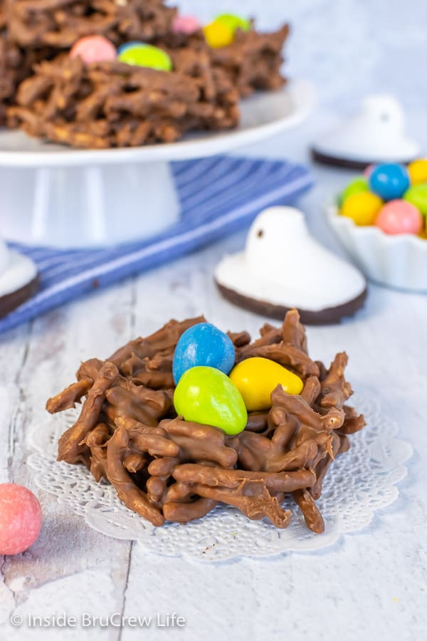 Close up picture of a chocolate nest cookie on a white doily with three candy eggs inside