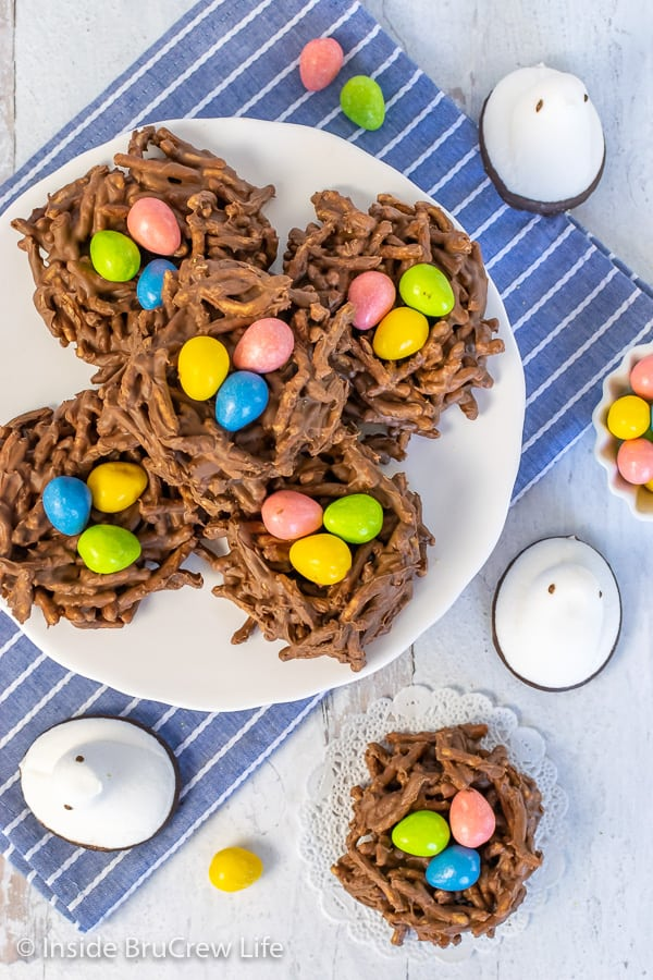 Overhead picture of chocolate nests on a white plate with colorful egg candies and white marshmallow Peeps