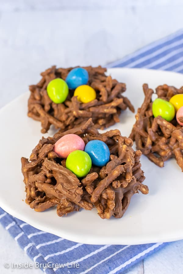 Three chocolate nests with colorful egg candies inside on a white plate