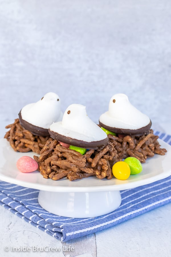 Three chocolate bird nest cookies with white marshmallow Peeps on top sitting on a white cake stand