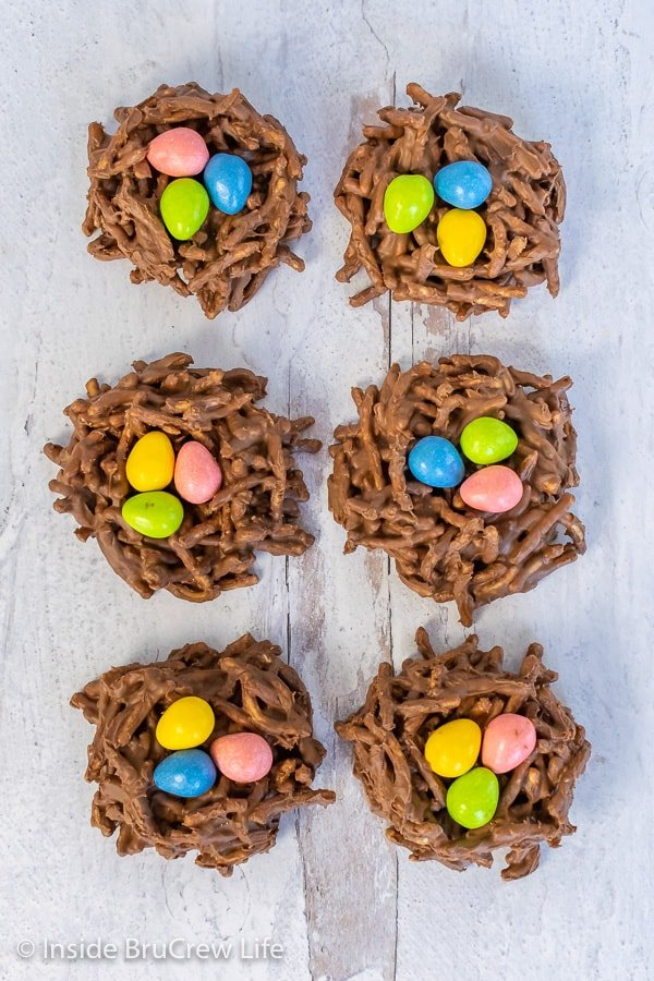 Overhead picture of 6 chocolate birds nest cookies with colorful candy eggs on a white board background