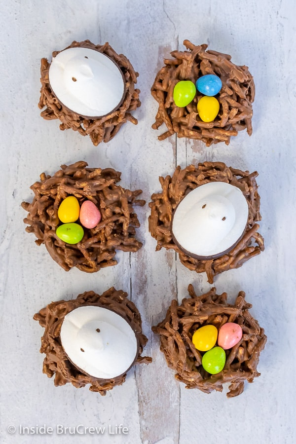 Overhead picture of 6 chocolate birds nests topped with candy eggs and marshmallow Peeps