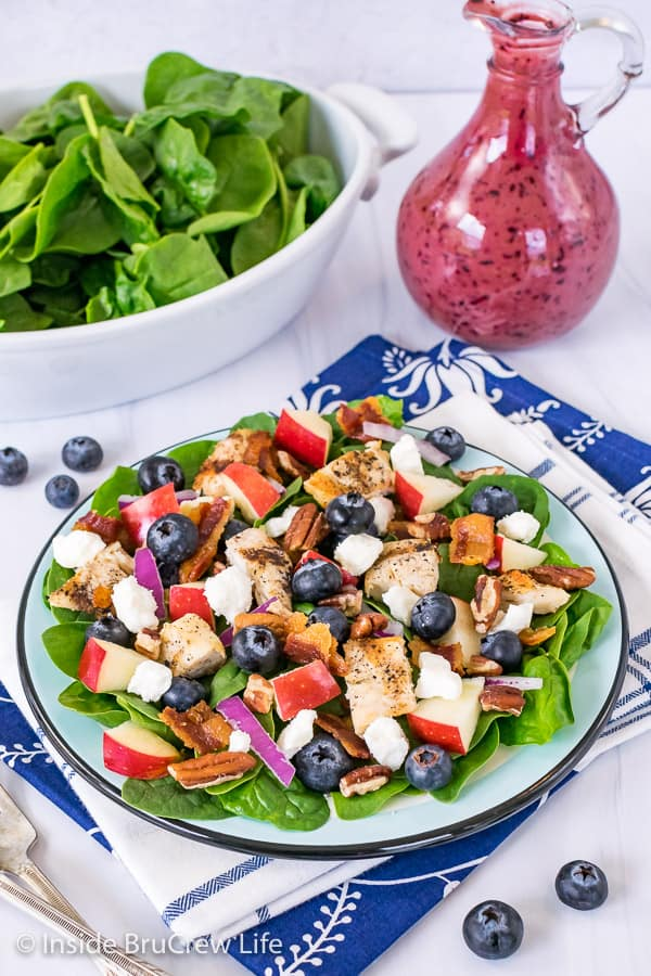 A blue plate on a blue towel topped with a spinach salad loaded with blueberries, nuts, cheese, and grilled chicken