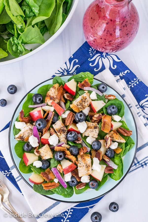 Overhead picture of a blue plate with a spinach salad topped with blueberries, apples, grilled chicken, nuts, and bacon