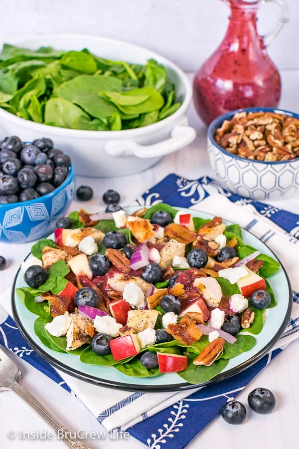 A plate of spinach salad topped with fruit, cheese, nuts, and grilled chicken with bowls of toppings behind it