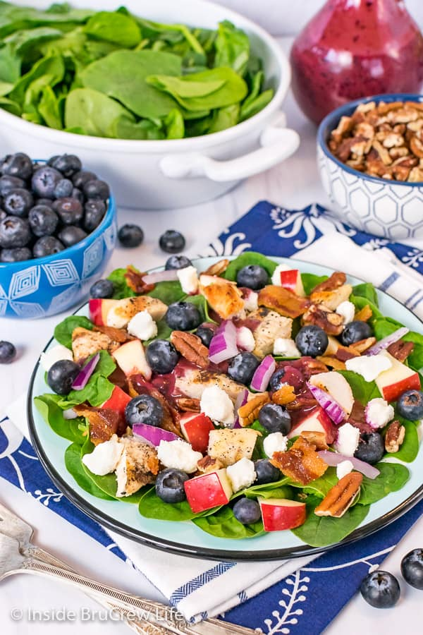 A close up picture of a blue plate with a spinach salad topped with blueberries, cheese, apples, and grilled chicken with bowls of toppings behind it