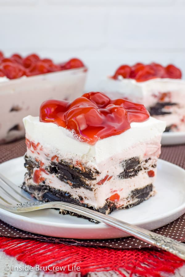 A square of cherry oreo icebox cake on a white plate with cherry pie filling on top and fork beside it