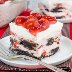 A white plate with a square of cherry Oreo icebox cake on it and cherry pie filling on top