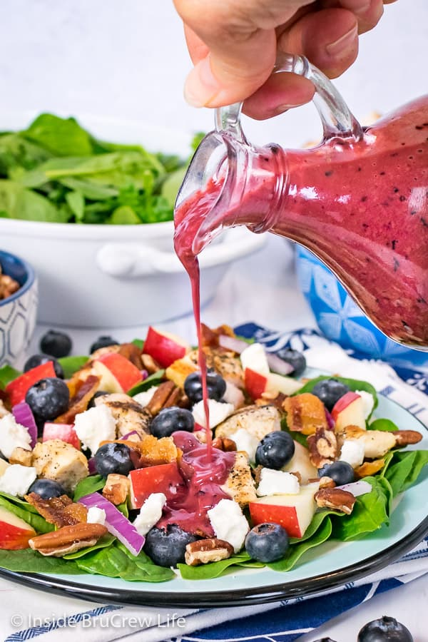 A jar of Blueberry Balsamic Salad Dressing being poured onto a spinach salad