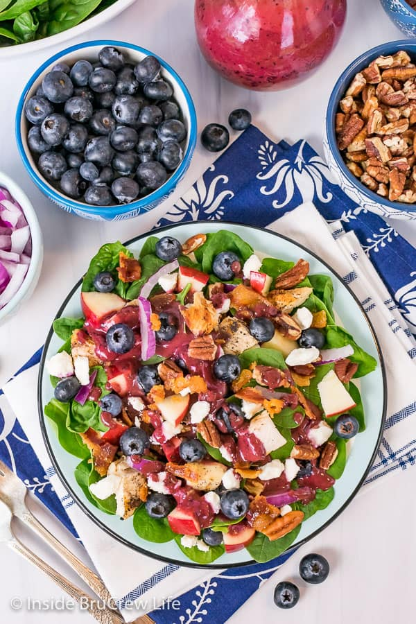 An overhead picture of a plate of spinach salad drizzled with Blueberry Balsamic Salad Dressing.